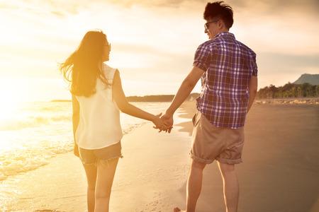 ビーチを楽しむ若いカップルが夕日で歩く 写真素材