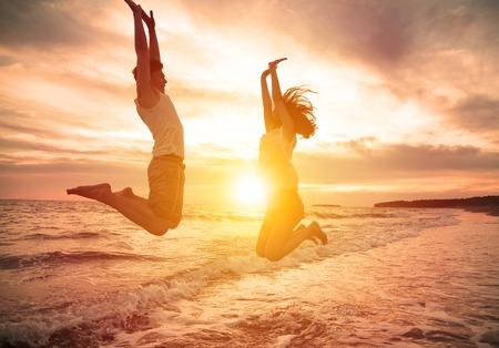 幸せなカップルのビーチでジャンプ