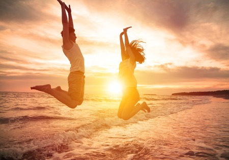 freedom nature: young happy couple jumping on beach