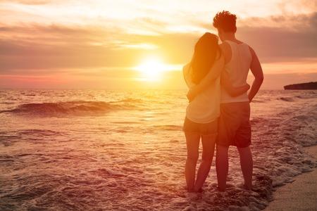 couple  amoureux: jeune couple en regardant le coucher du soleil sur la plage Banque d'images