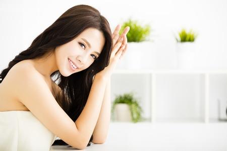 lächelnde junge schöne Frau sitzt im Wohnzimmer