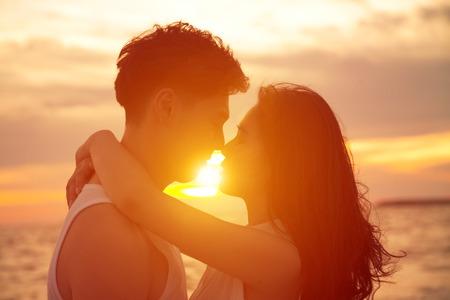 femme romantique: jeune couple embrassant sur la plage au coucher du soleil