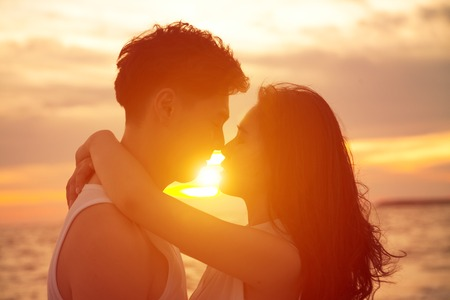 siluetas de enamorados: joven pareja besándose al atardecer en la playa