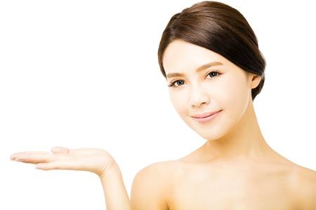 visage: belle jeune femme montrant des produits de beauté espace vide sur la main