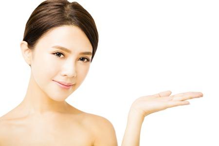 красота: Красивая молодая женщина, показывая продукт красотки пустое пространство под рукой Фото со стока
