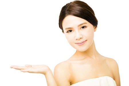beauty: Mulher nova bonita que mostra o produto de beleza espa