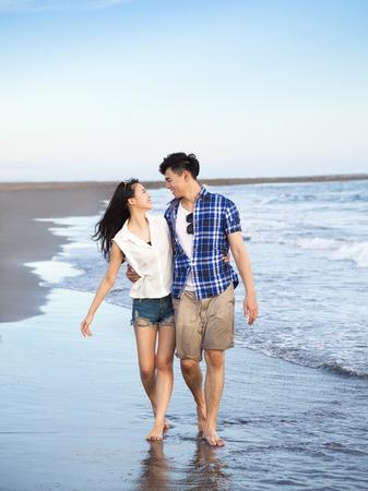 feliz joven pareja caminando en la playa