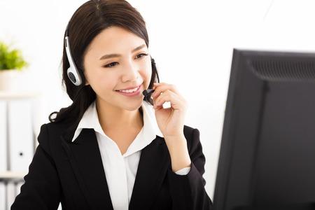 trabajadores: joven mujer de negocios hermosa con un aud�fono en el cargo Foto de archivo