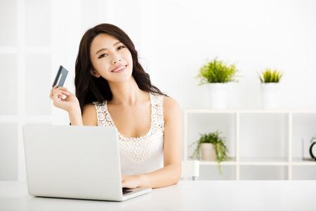 chillen: Junge Frau, die online mit Kreditkarte und Laptop