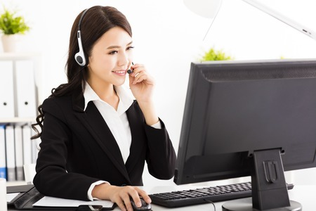 contact center: young beautiful  business woman with headset in office