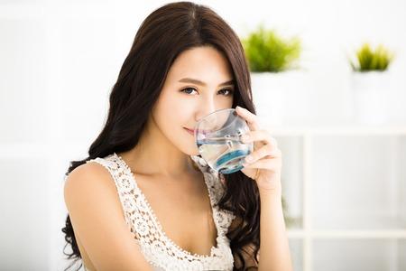 entspannte junge lächelnde Frau trinken sauberes Wasser Standard-Bild