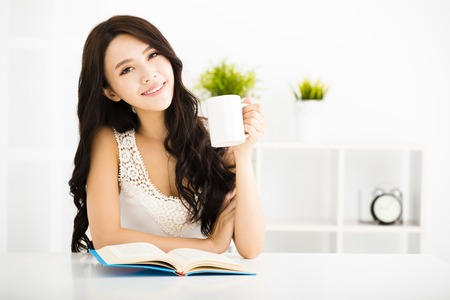 Happy young woman reading book in living room photo