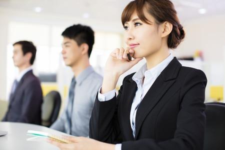 Geschäftsfrau, die mit ihren Mitarbeitern im Konferenzraum Standard-Bild