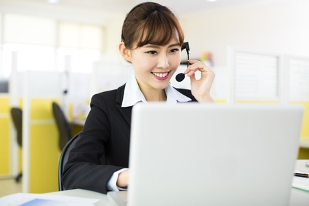 hotline: young beautiful  business woman with headset in office