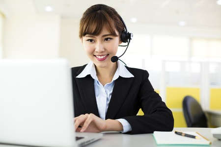 customer assistant: young beautiful  business woman with headset in office