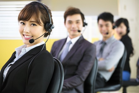 to phone calls: young business people working with headset in office