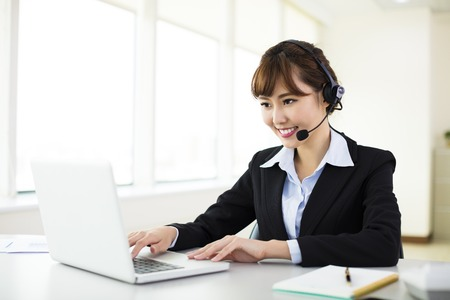 servicio al cliente: joven y bella mujer de negocios con kit manos libres portátil en la oficina Foto de archivo
