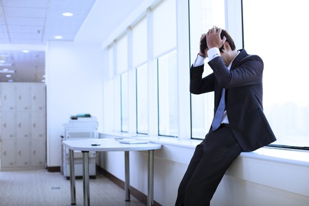 asian professional: Depressed young businessman in office