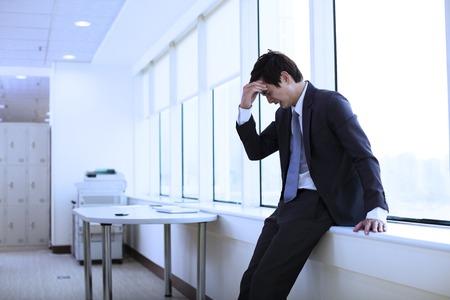 dolor de cabeza: Joven hombre de negocios deprimido en el cargo Foto de archivo