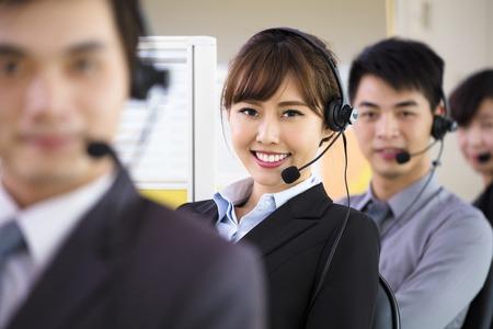 servicio al cliente: jóvenes empresarios que trabajan con auriculares en la oficina Foto de archivo