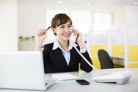 mujer trabajadora: mujer de negocios hablando por teléfono en la oficina