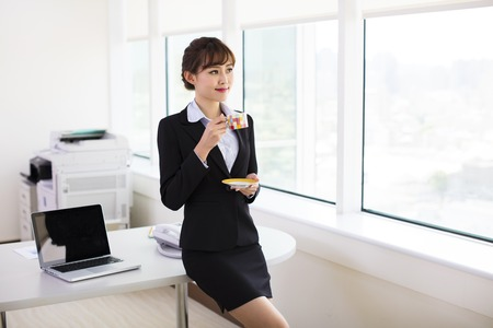 asian lady: relaxed  businesswoman drinking coffee in the office