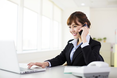 smile girl: businesswoman talking on the phone in the office