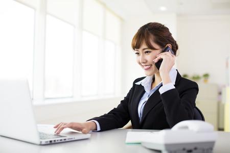 počítač: podnikatelka mluvit na telefonu v kanceláři Reklamní fotografie