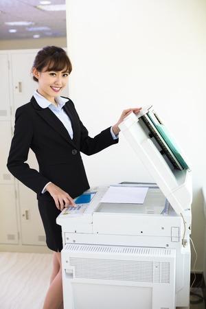 fotocopiadora: bastante joven secretaria que usa la máquina de fotocopias en la oficina