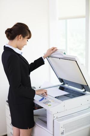 オフィスのコピー機を使用して若い実業家