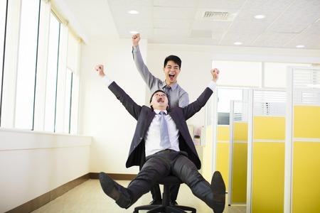 empujando: gente de negocios feliz que se divierten en la oficina