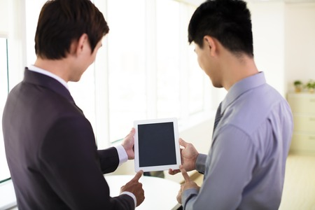 business partners looking at tablet and discussing photo