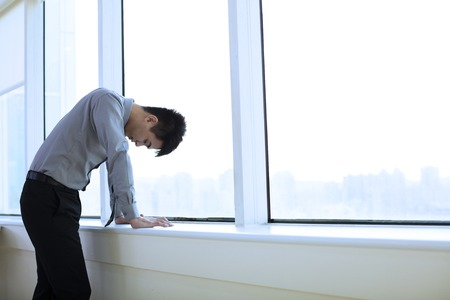 man head: Depressed young business man  in office Stock Photo