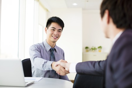 negocio: Hombre de negocios que sacude la mano en la oficina