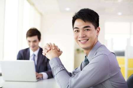young smiling businessman working in office photo