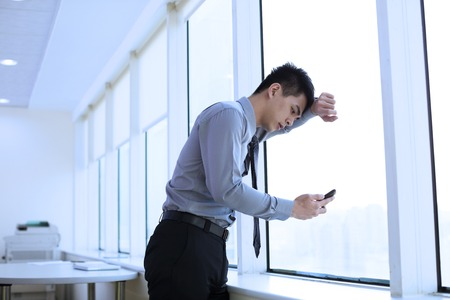 worried businessman: Depressed young businessman looking smart phone in office