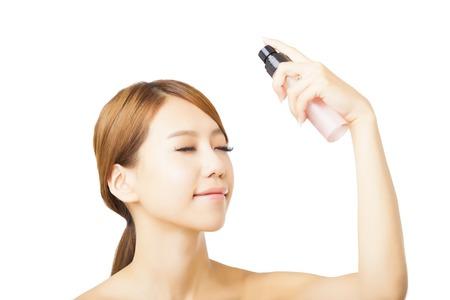 Bella donna che applica il trattamento delle acque di spruzzo sul viso Archivio Fotografico - 42801629