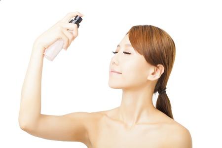mujer maquillandose: Mujer hermosa que aplica el tratamiento del agua de rociado en la cara