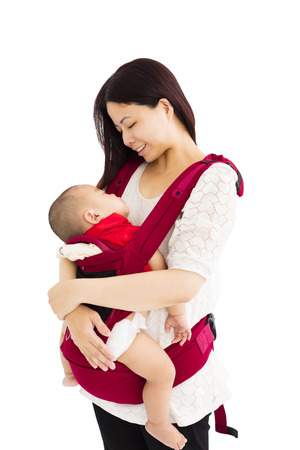 carrying: mother holding a baby in a baby carrier