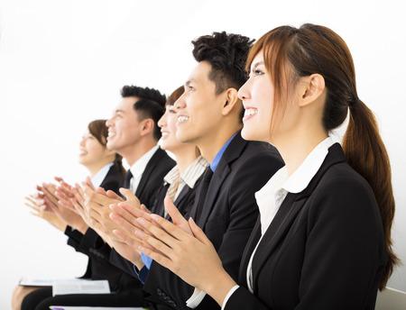 personas saludandose: La gente de negocios sentado en una fila y aplaudiendo Foto de archivo