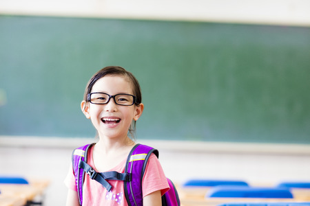 education: heureuse petite fille dans la salle de classe