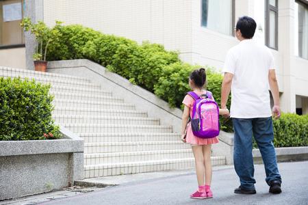espalda: Padre que recorre a la escuela con los niños Foto de archivo