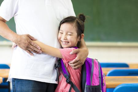 salon de clases: Ni�a feliz abrazando a su padre en el aula