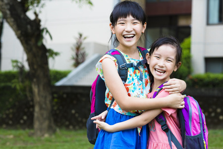 backpack: happy little girls with classmates having fun at the School Stock Photo