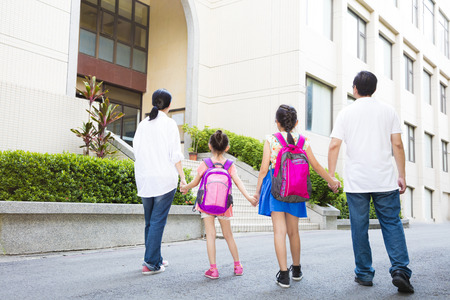 parent child: Father and mother Walking To School With Children Stock Photo