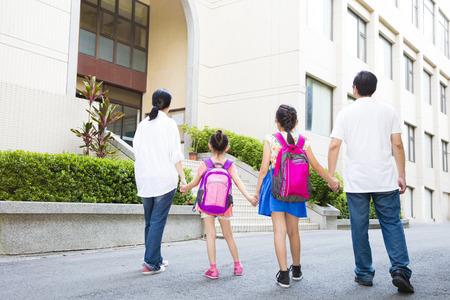 espalda: Padre y madre caminando a la escuela con los niños