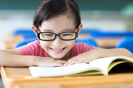 girl glasses: happy little girl studying in the classroom