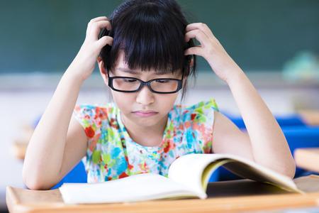 Depressed little girl studing in the classroom Standard-Bild