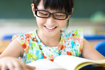 glückliches kleines Mädchen, das Studium im Klassenzimmer