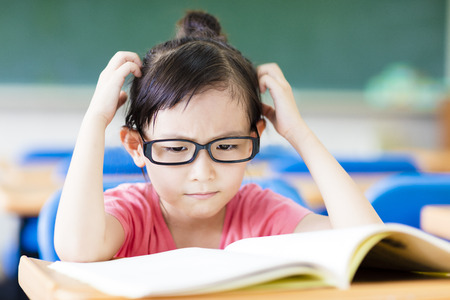 Depressed little girl study in the classroom